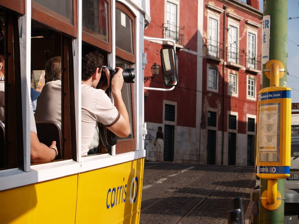 tourist taking pictures in a lisbon tram